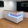 Manhattan reception desk is shown here with a White Matte Laminate Base, Walnut Wood Veneer recessed panel and counter top with a brushed aluminum toe-kick.