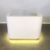 Nola Custom Reception Desk is shown here with a white Gloss Laminate Base and aluminum Toe-kick and Color changing LED light.